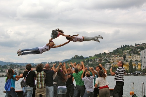 A group of youth tossing three teens in the air. Not photoshoped.